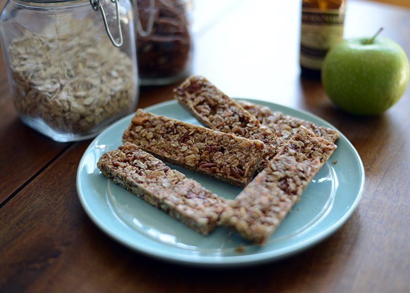 Apple Pie Granola Bars sitting on a blue plate with a green apple and oatmeal in the background